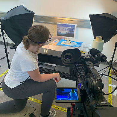 Artist working on an animation of two penguins, film camera and lights