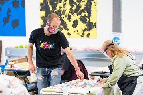 Staff helping artist create drawing on desk