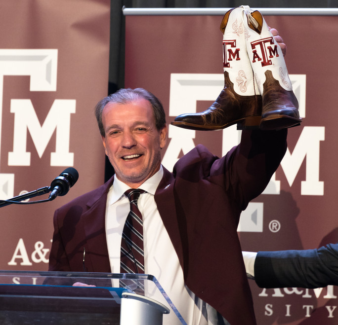 Jimbo Fisher lifts up a pair of A&M cowboy boots that were given to him as a gift after being introduced as new head coach Dec. 4, 2017.