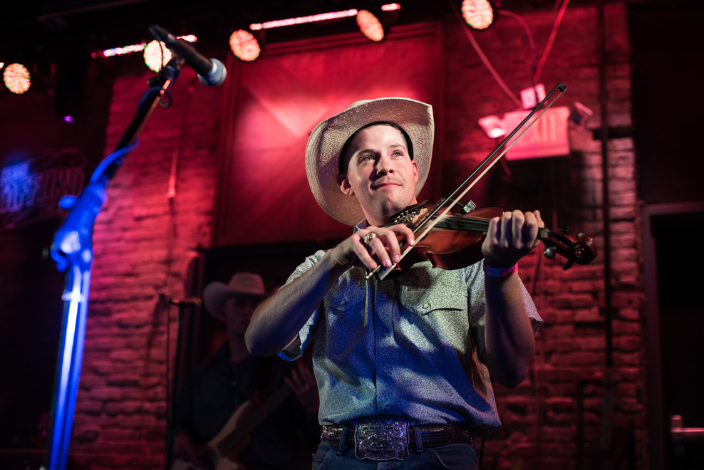 Adam Hill plays his fiddle during a concert with his band, Prairie Switch, at Grand Stafford Theater in Bryan, Texas.