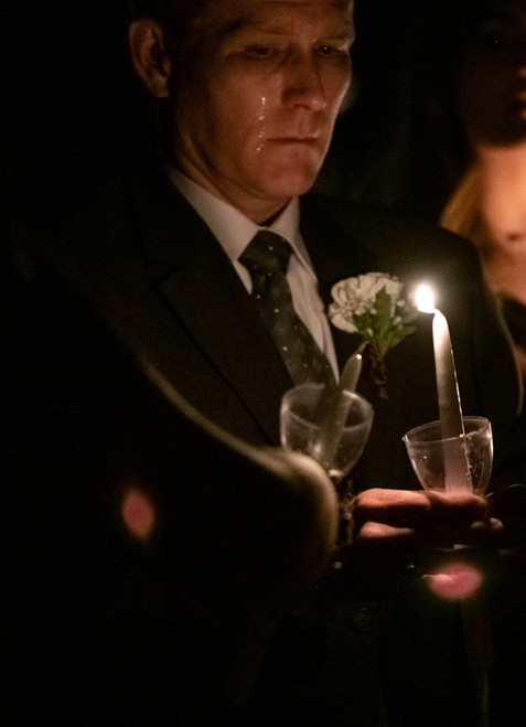 A tear slides down a man's cheek as he lights a candle in honor of a loved one who passed away at the campus Muster ceremony on April 21, 2019.
