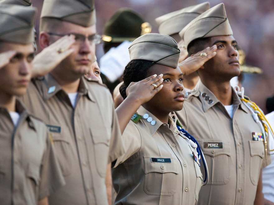 Members of the Texas A&M Corps of Cadets salute the flag as the National Anthem is played before a football game.