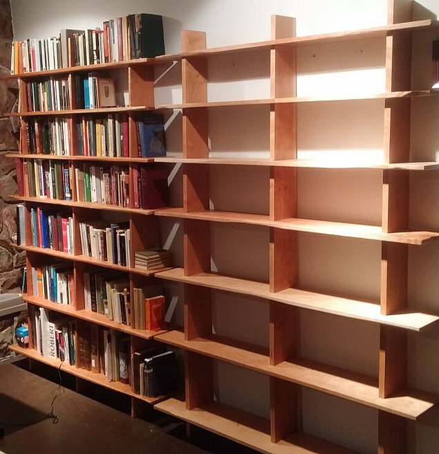 two leaning cherry bookcases