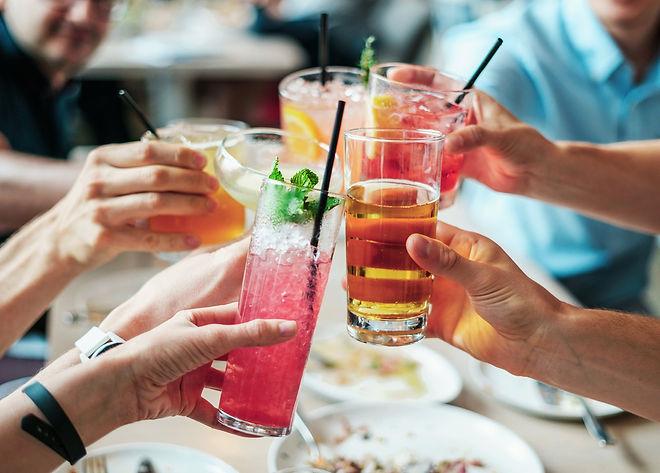 Folk som skålar med färgglada drinkar