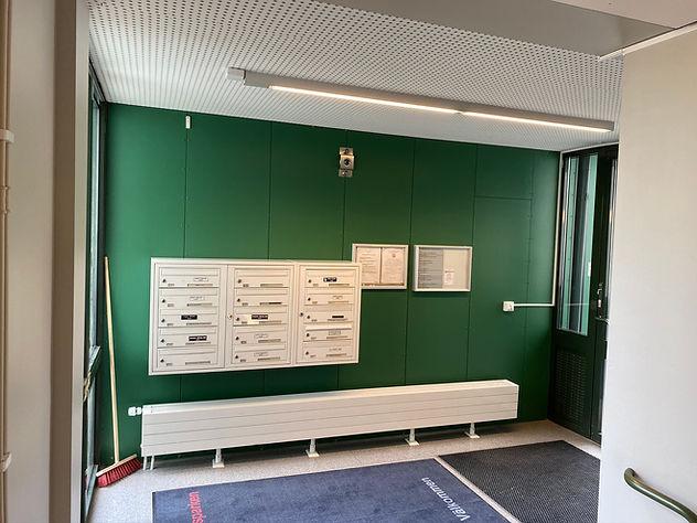 Brevlådor på grön vägg