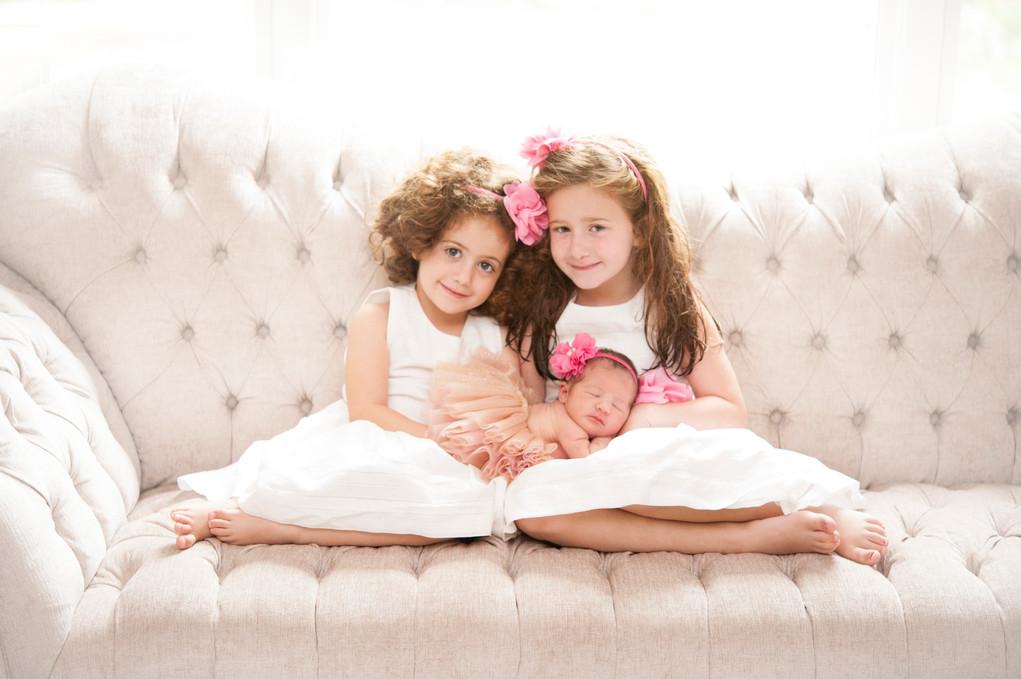 Sisters holding newborn baby girl