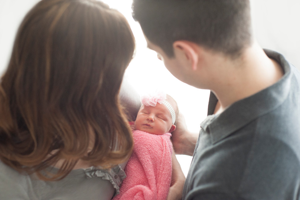 Mom and Dad looking down on their newborn baby