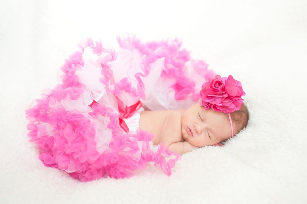 Newborn photo of baby wearing headband and tutu