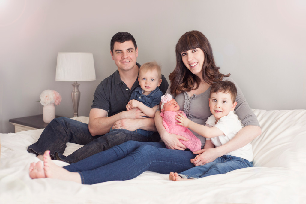 Family Newborn Session posing on bed