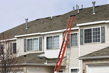 Ladder leaning against a building to facilitate a roof inspection.