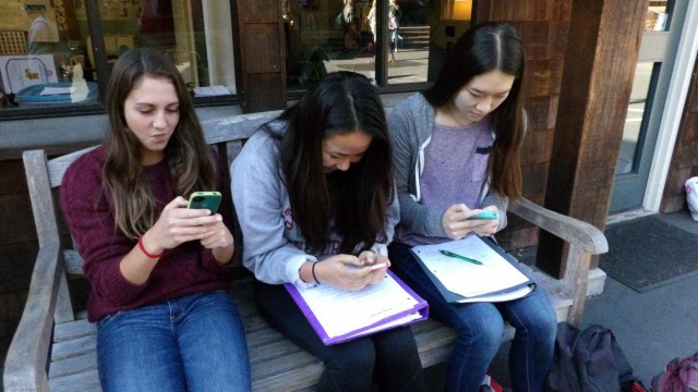 Three seniors kill some time on their iPhones. Photography by Malaya Jules
