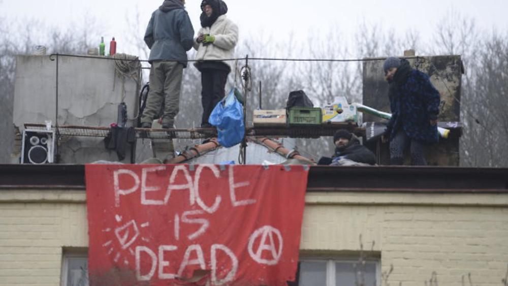 Poněkud nevhodný banner na střeše vyklízeného squattu Šatovka (2018)