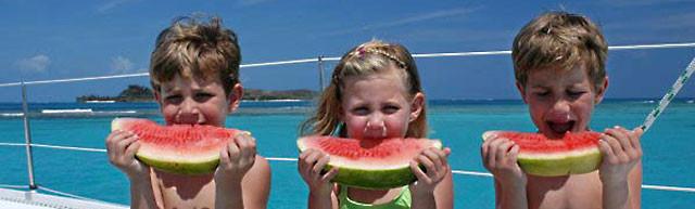 Дети на яхте едят арбуз
