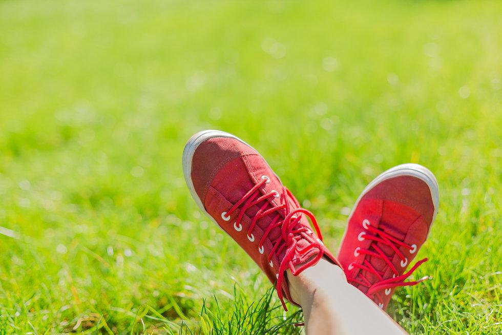 Feet in sneakers in green grass. Summer