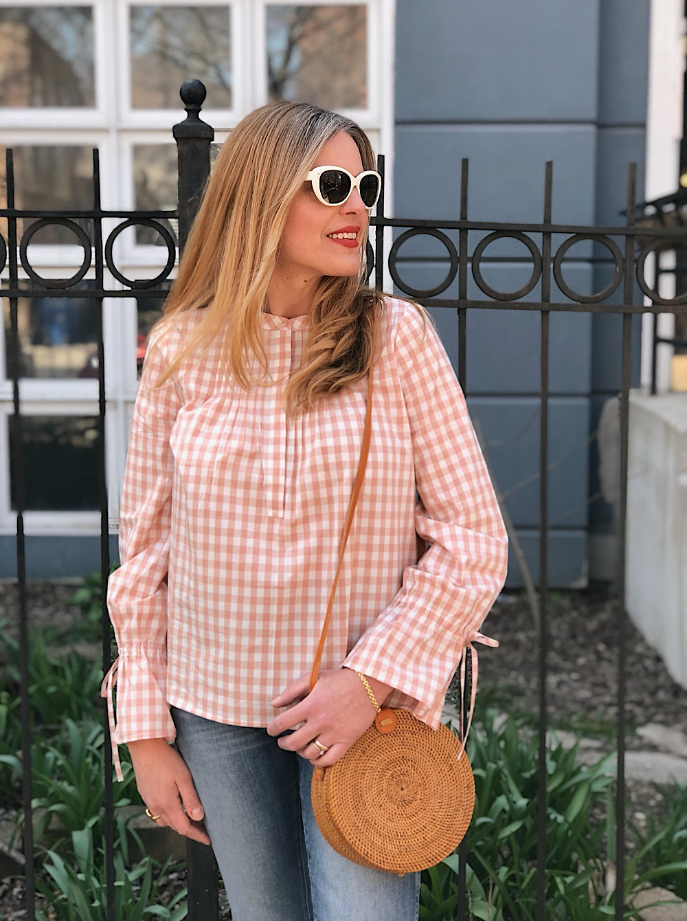 blond woman, white sunglasses, blush gingham top, jeans, straw bag