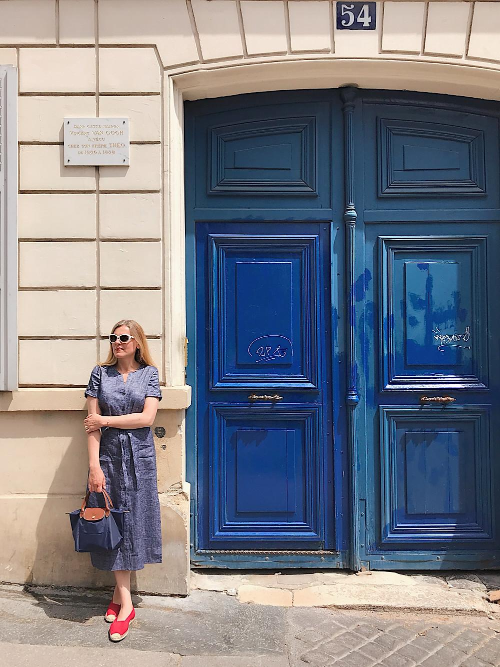 woman next to blue doors
