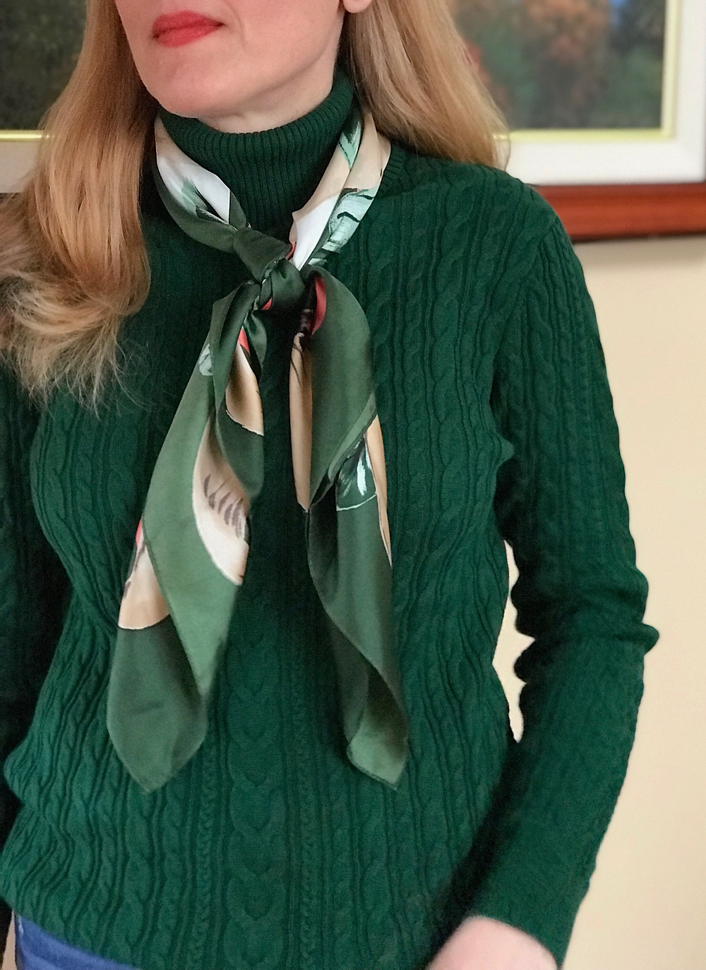 blond woman in a green turtleneck sweater with silk scarf
