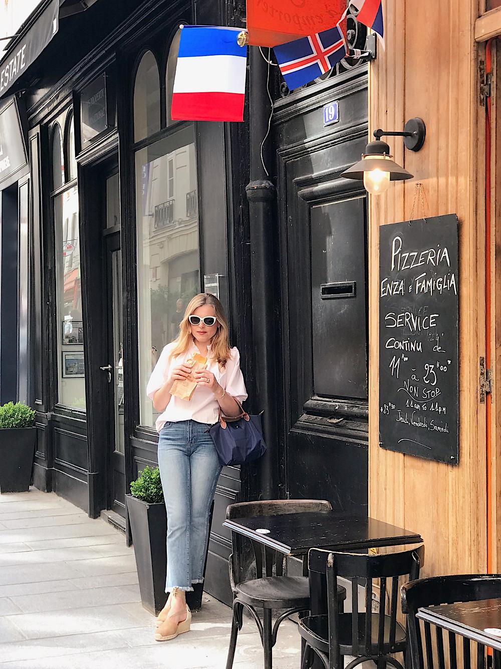 woman on Paris street holding croissant