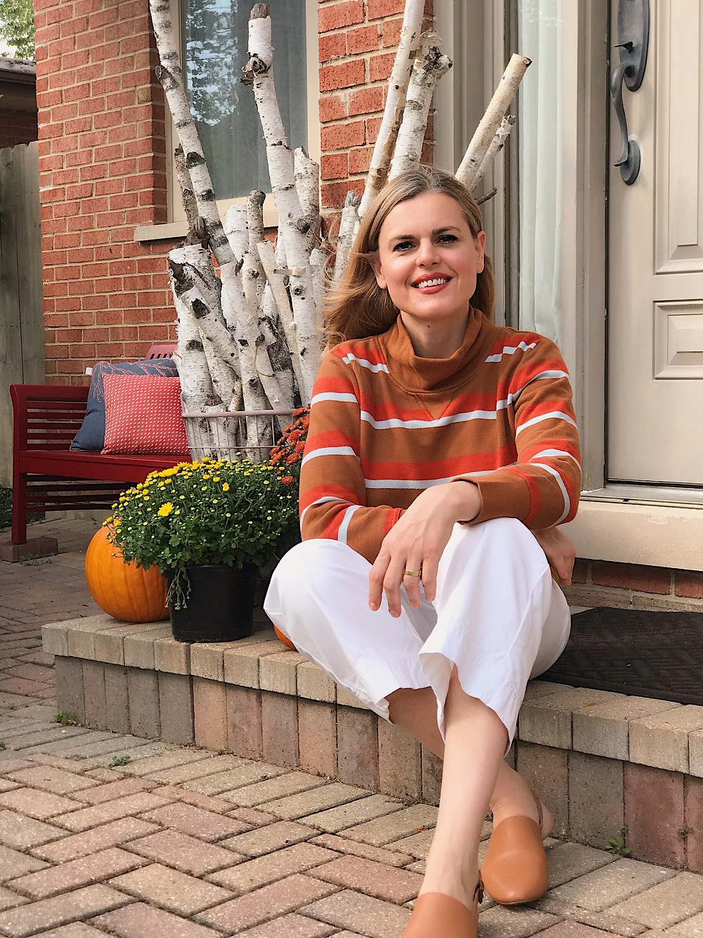 blond woman sitting  on a front step with mums and pumpkins