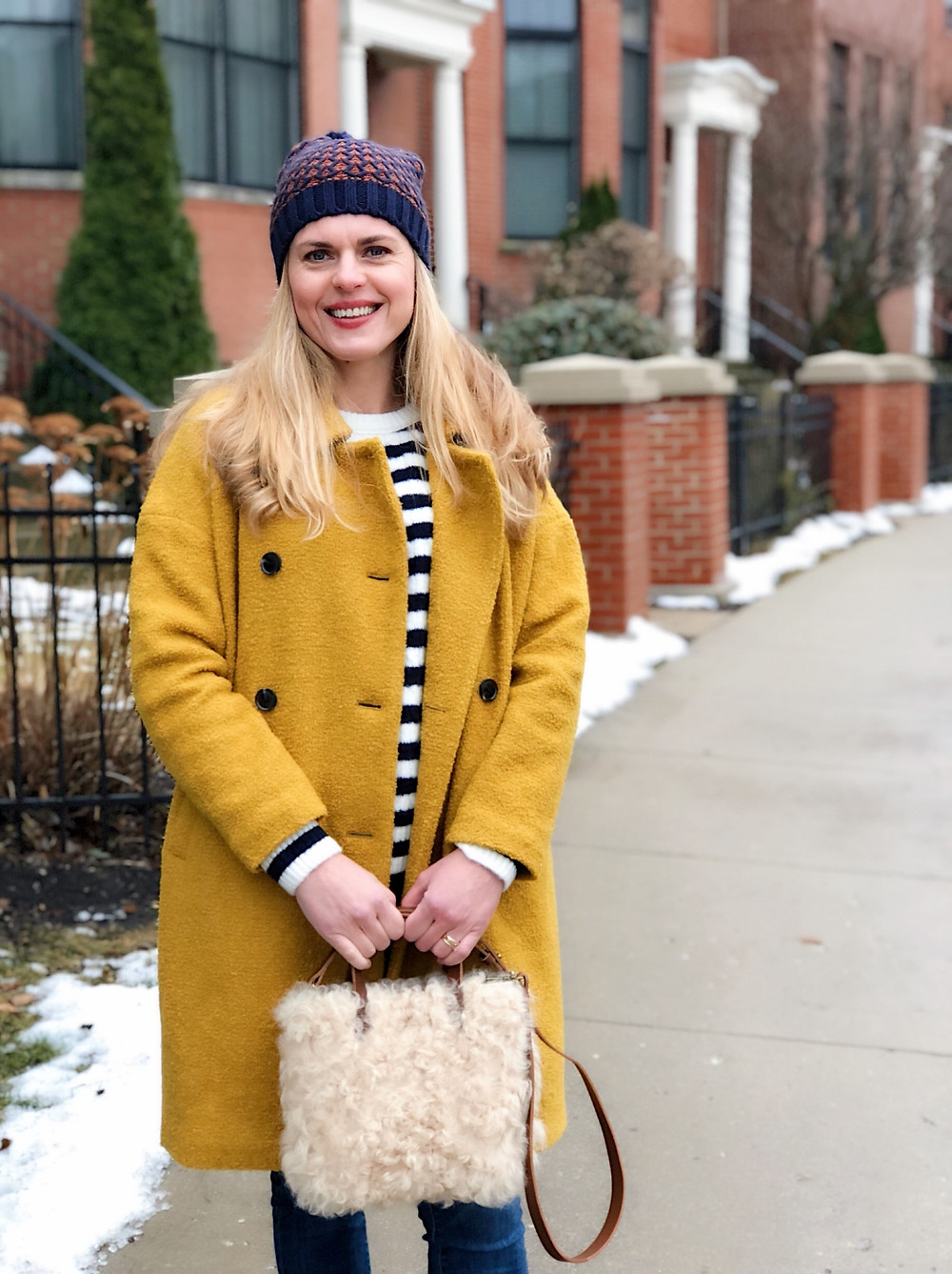 mustard yellow coat, striped sweater, jeans, shearling bag