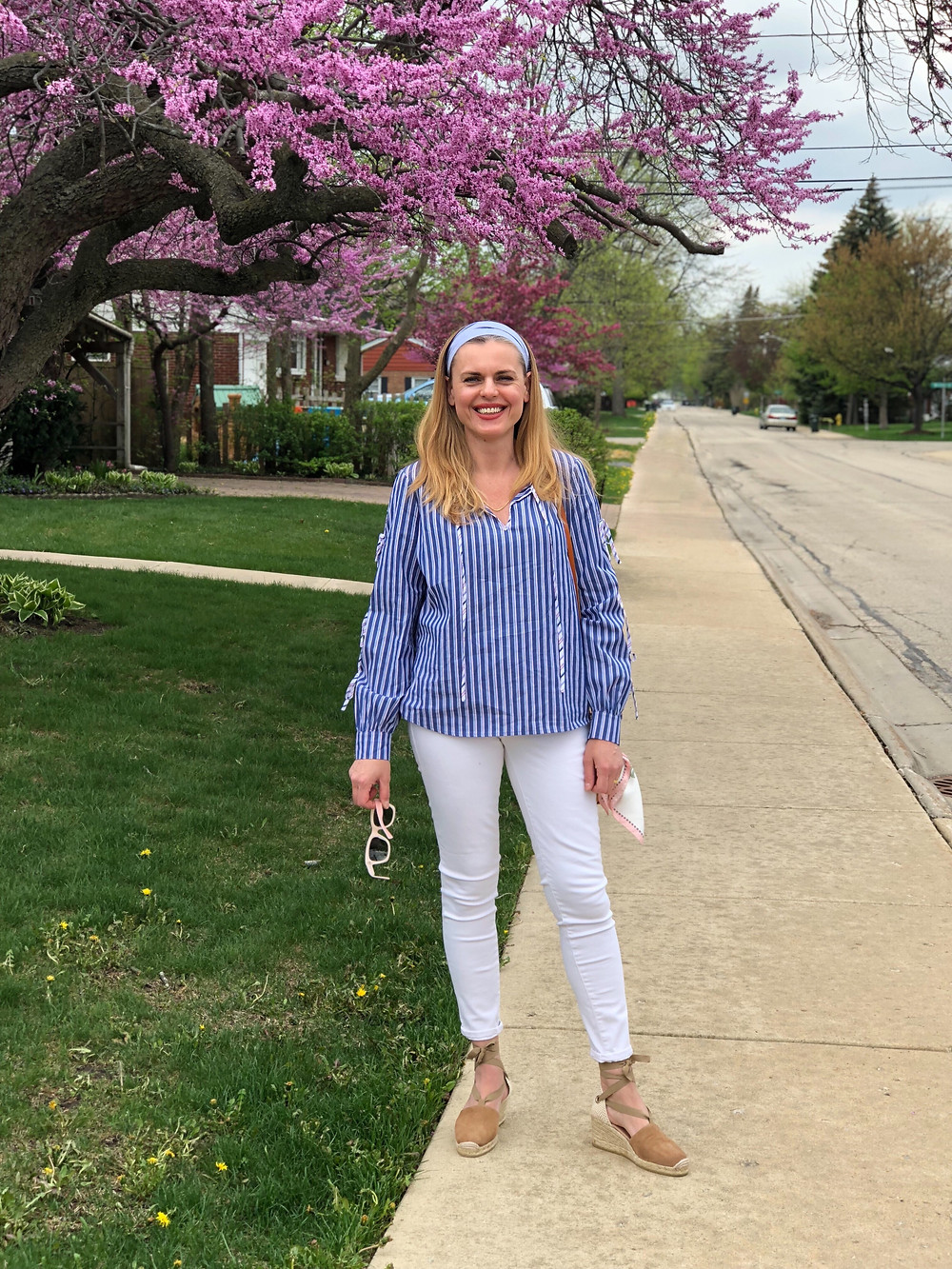 blond woman in blue top and white jeans under a blooming tree