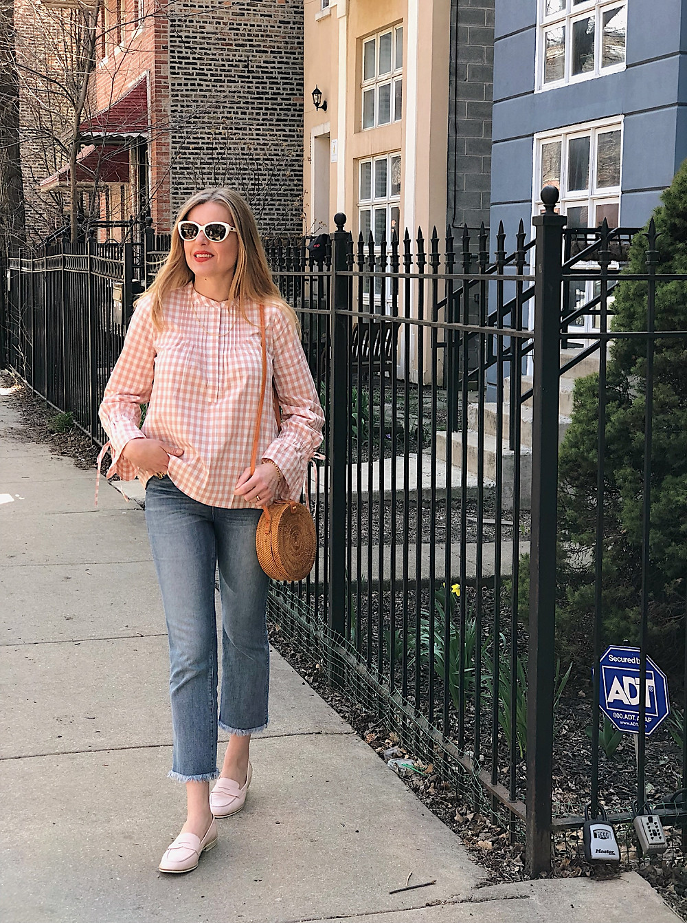 blond woman, blush gingham top, white sunglasses, jeans, straw bag