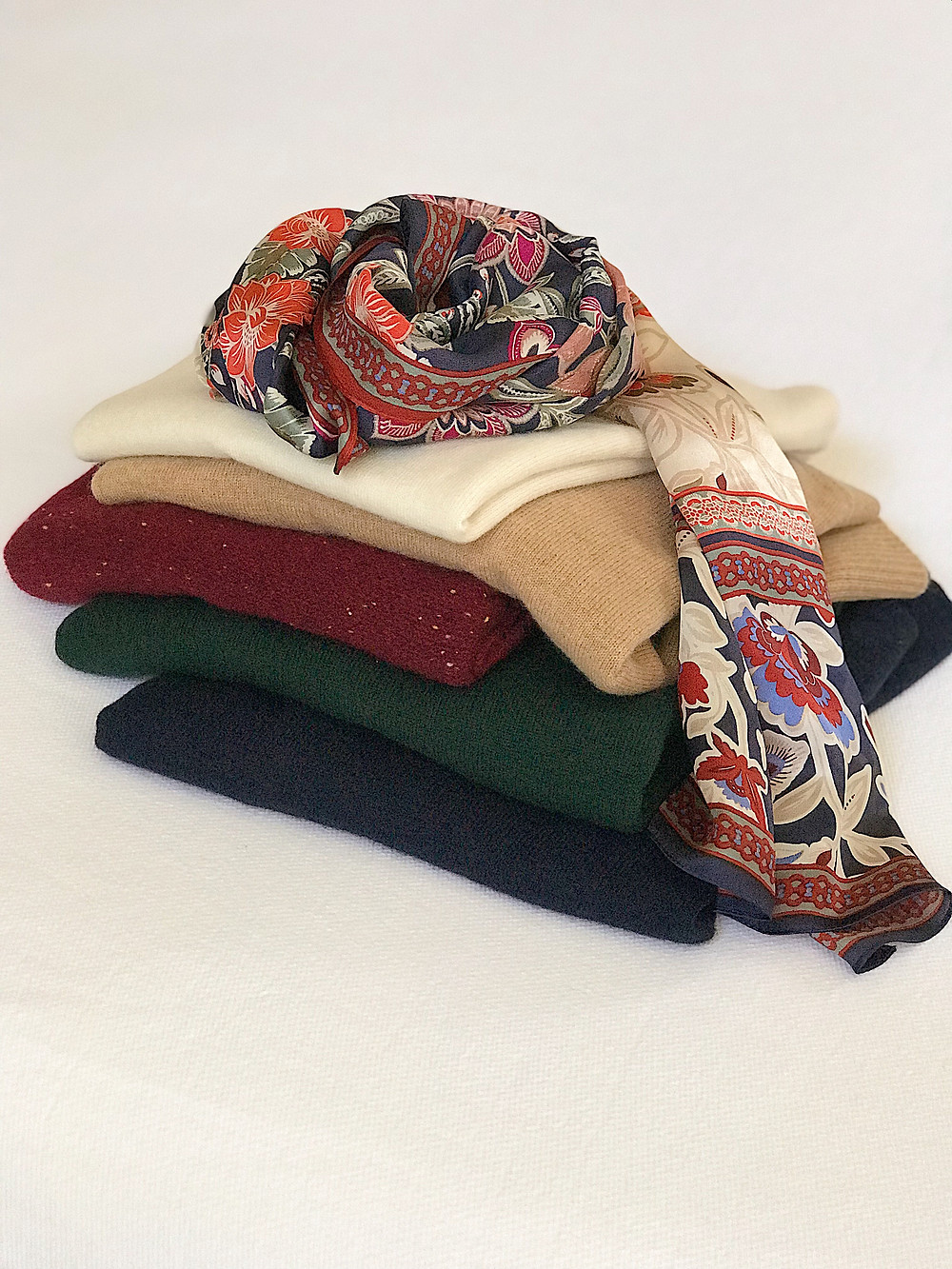 stack of folded sweaters in autumn hues