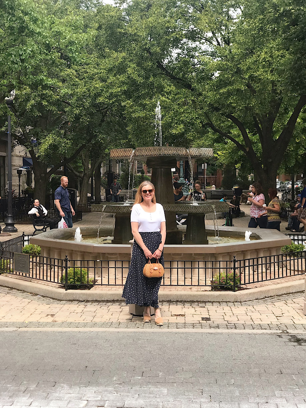 woman standing in front of a decorative fountain