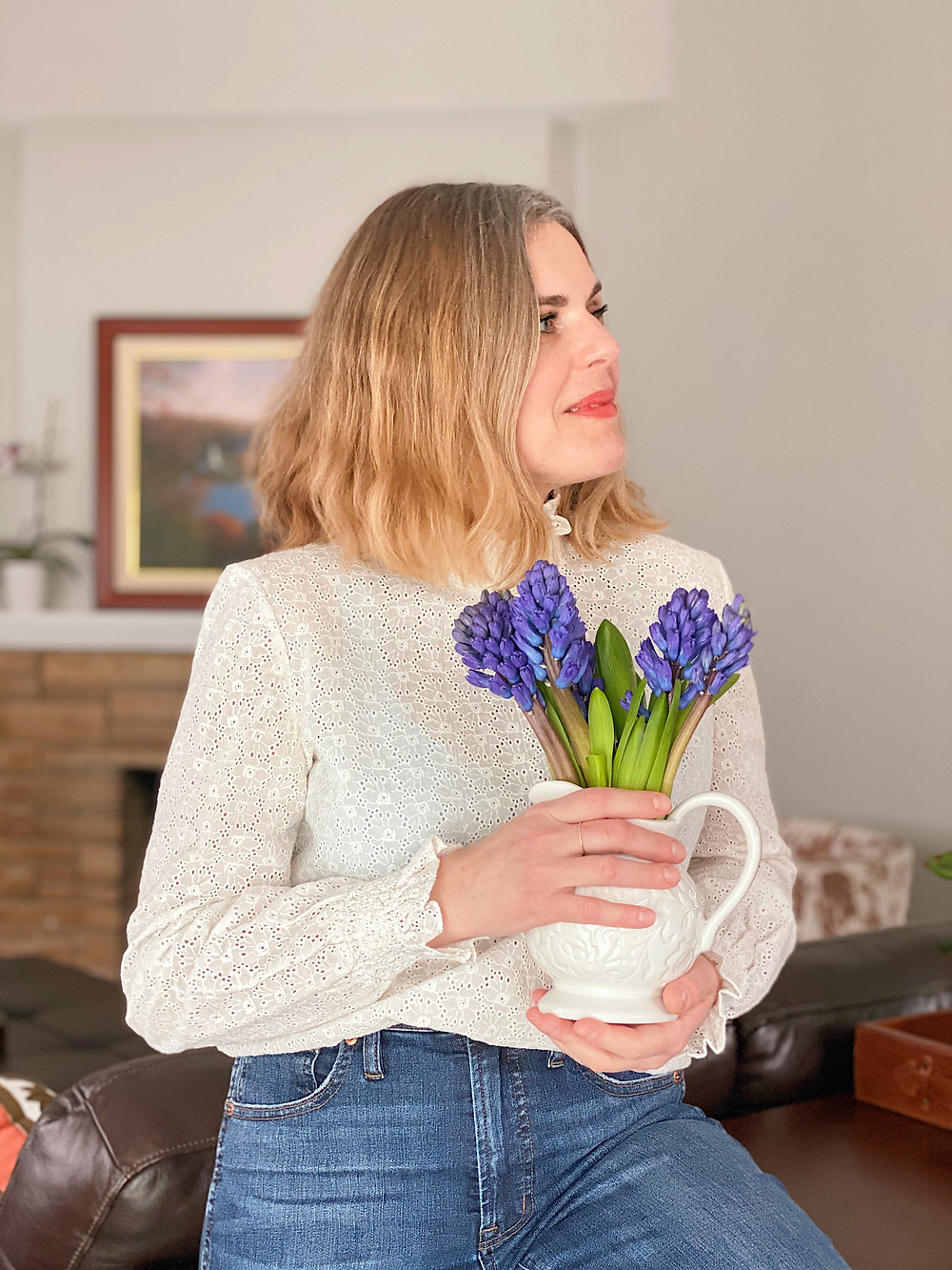 Blond woman smiling and holding a bouquet of hyacinth