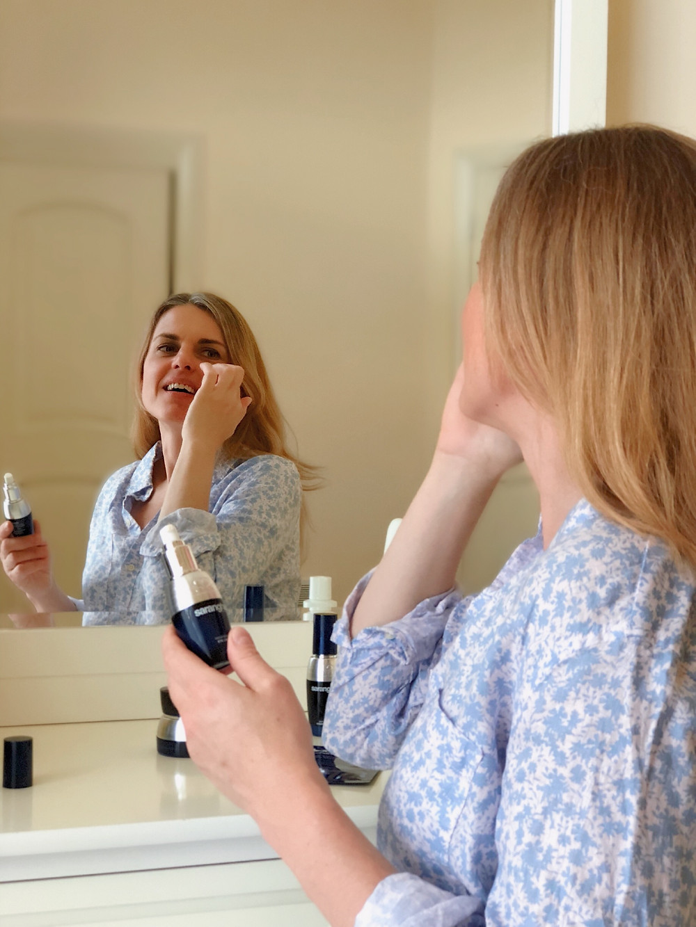blond woman applying face cream