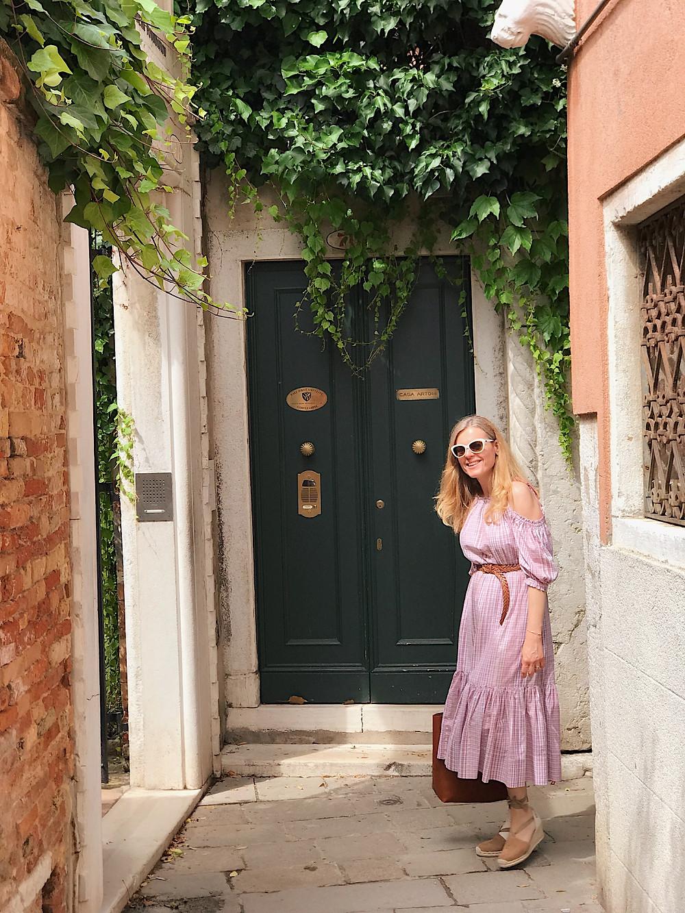 woman in pink dress on small Venetian street