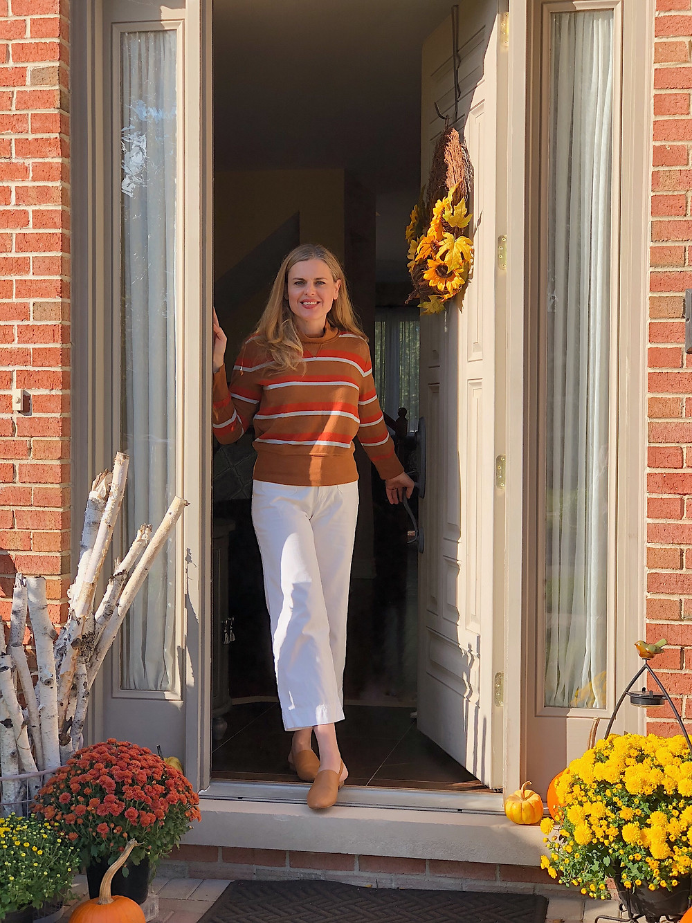 blond woman in doorway decorated for fall