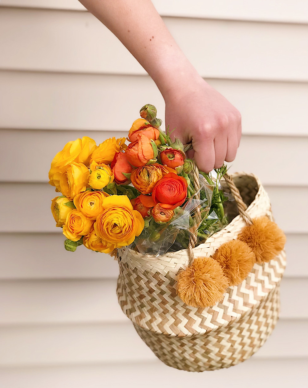 hand holding basket of flowers