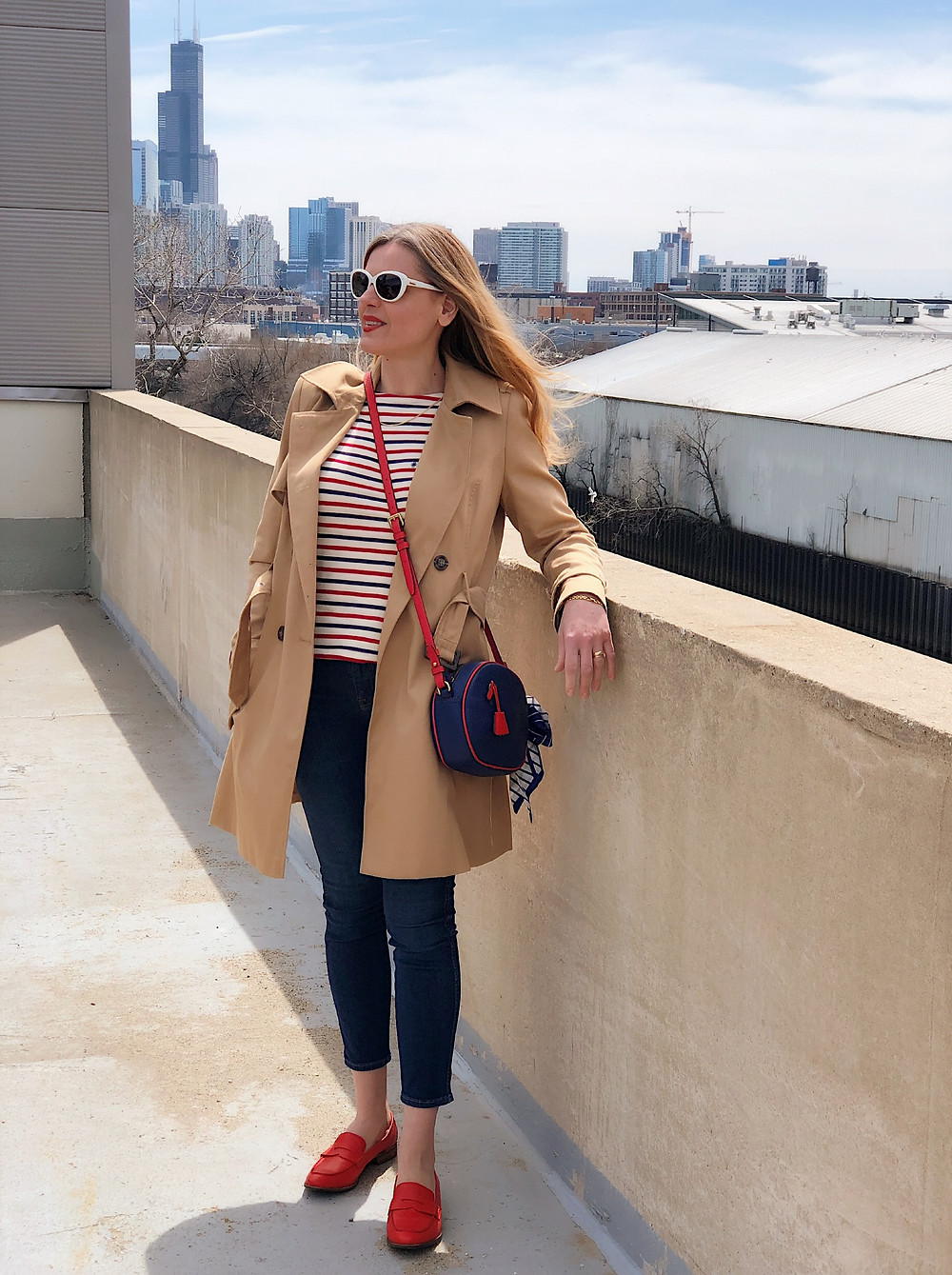 woman in trench coat, striped tee, white sunglasses, blue and red purse