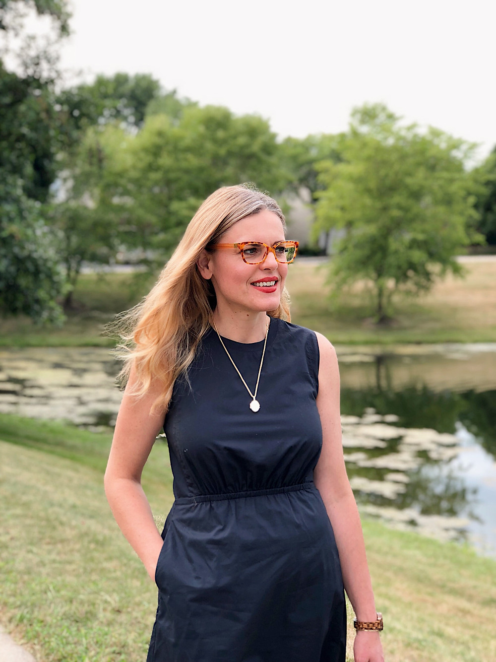 woman in navy dress and tortoise glasses by a pond