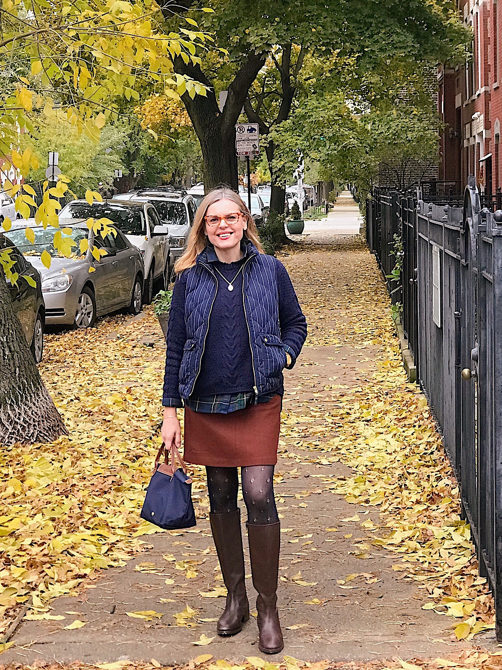 blond woman in brown skirt, navy sweater and vest on a street