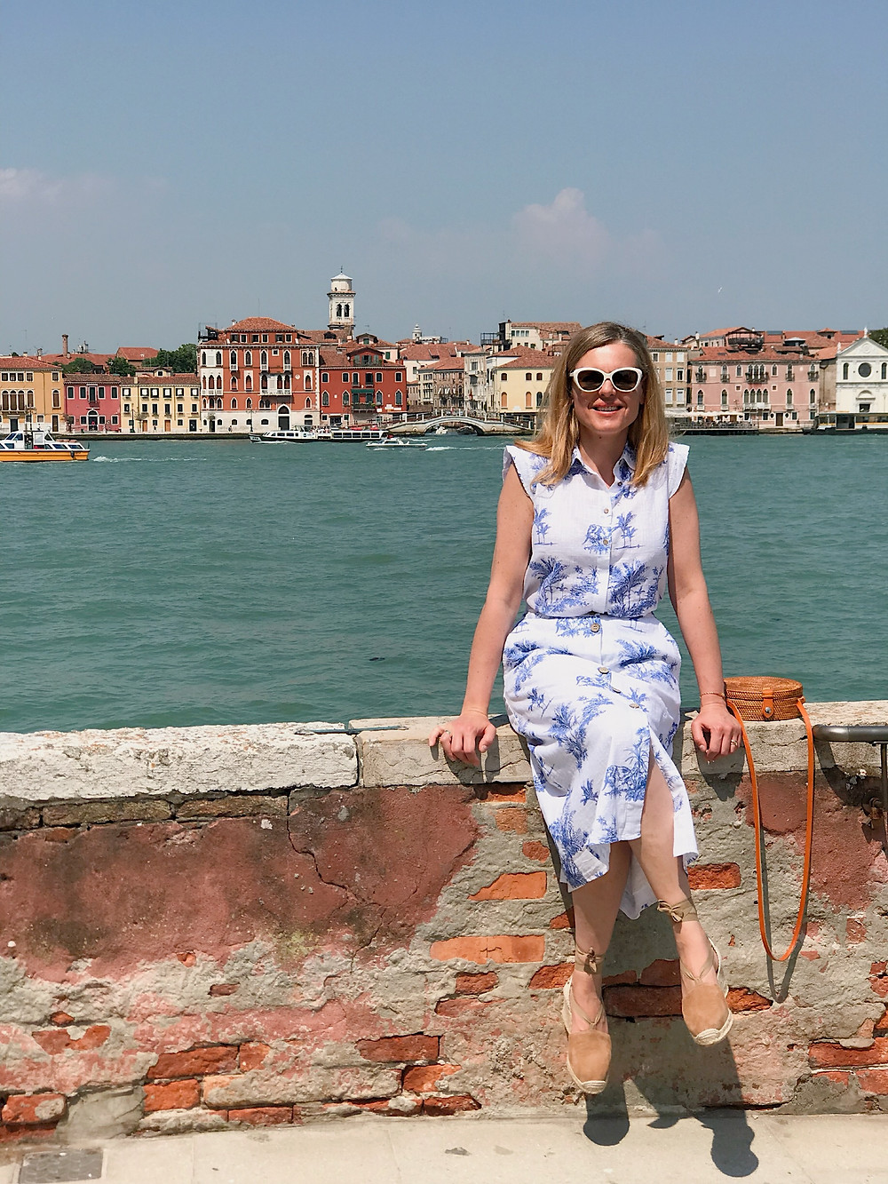 woman sitting on brick wall overlooking Venice