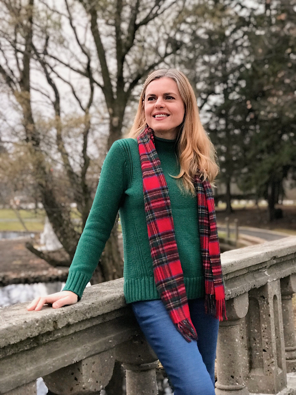 blond woman in green sweater and red plaid scarf
