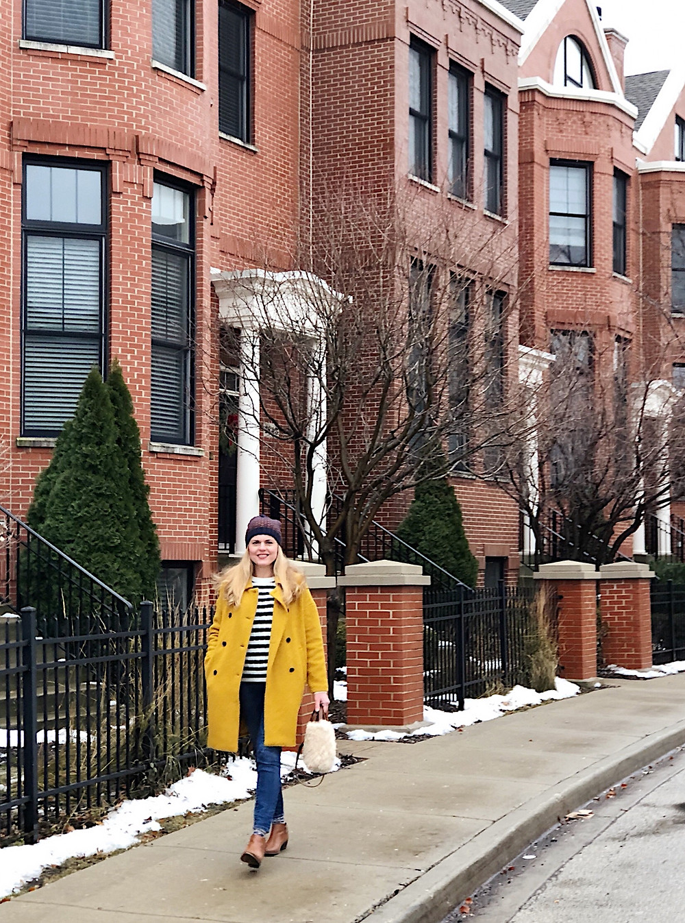 Patricia wearing mustard yellow coat, striped sweater, jeans, booties and shearling tote bag