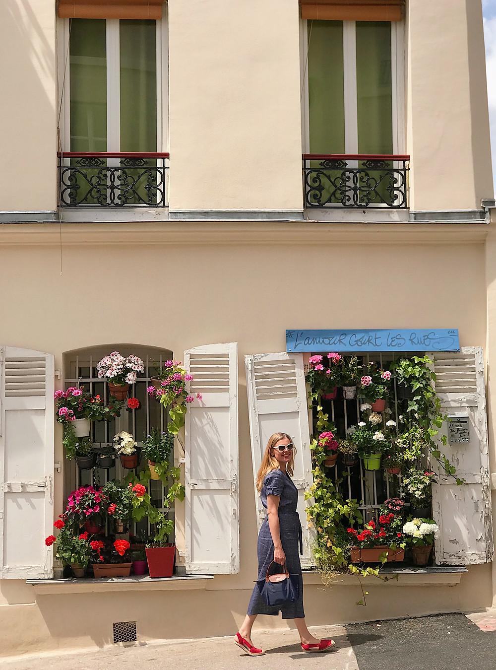 woman walking in front of windows full of flowers