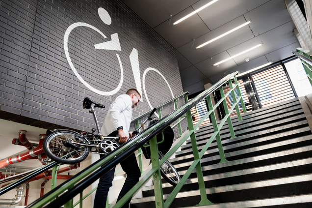 man walking upstairs with bike commercial photography derby