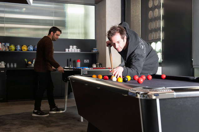 Man playing pool in corporate office photography