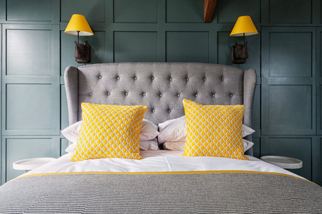 grey bed with yellow cushions