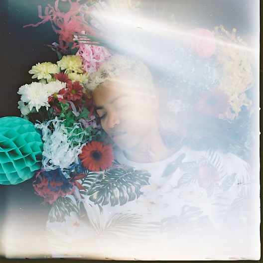 Centre frame a young mixed race man with bleached dyed blond hair wears a white jumper with a floral pattern on it, only his upper body in frame. His eyes are closed, he is lying down, seen from above and his head is surrounded by colourful flowers and paper decorations. A light leak runs vertically on the right side of the frame.