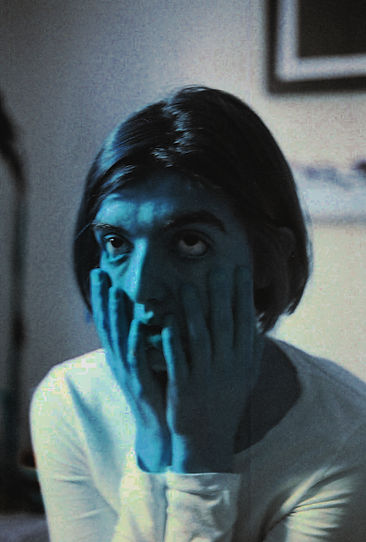 Centre frame is a woman with hands on her face pulling down the skin on her cheeks under her eyes. Her mouth is open and her eyes delirious. She has short dark hair and wears a long sleeved white top.  As the photo is shot in blue duo-chrome her skin and hair are light blue as well as the general hue of the photograph.