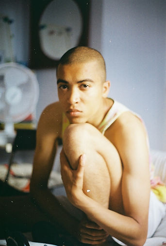 A young mixed race man sits centre frame his left knee bent with his head resting on top. His left arm clasps his knee. He has short hair and stares into the camera. He wears a yellow vest. In the background is a white fan and an oval mirror in a dark frame.