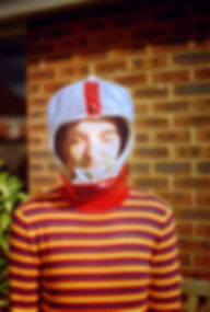 Centre frame is a young white woman with her eyes closed as a strong ray of light shines on her face. She has brown hair which is obscured by a silver and red children's space helmet. She wears a striped red, blue and yellow jumper, only her upper body in frame. Behind her is a brown brick exterior wall and a green plant. The photo has a thin black border.