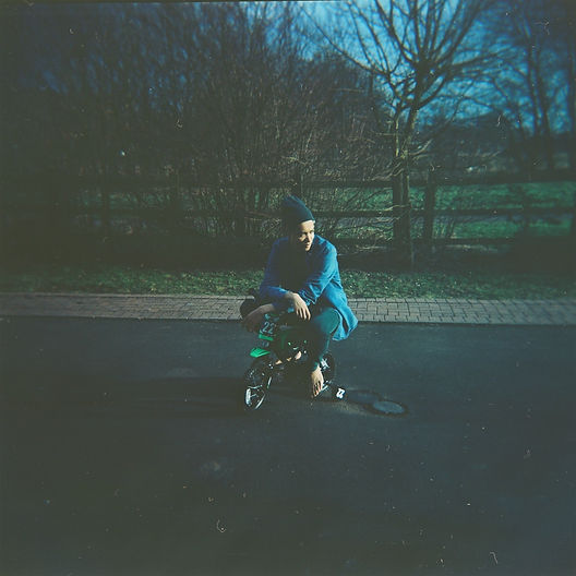 An underexposed image of Oscar, a mixed race man in his twenties, wearing dark blue casual clothing and a dark green beanie hat. He is outside on a residential road, in front of a fence and leafless winter trees. He is sitting on a child's tricycle without shoes on, looking away from the photographer to the right of the image.
