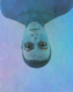 A young mixed man is centre frame upside down, only his bare shoulders and above in frame. The entire frame is blue and white paint is on his face. His eyes are open and stare directly into the camera. Faint lines run horizontal across the frame.