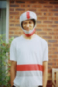 Centre frame stands a young mixed race man, only his upper half from his waist is in frame. He wears a white t-shirt with a red and a grey stripe running across the front. He wears a child's' silver, grey and red space helmet and squints at the camera. A brick wall is behind him and a green plant.
